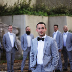 groom posing with groomsmen in the background