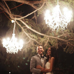 couple hugging under chandelier outside