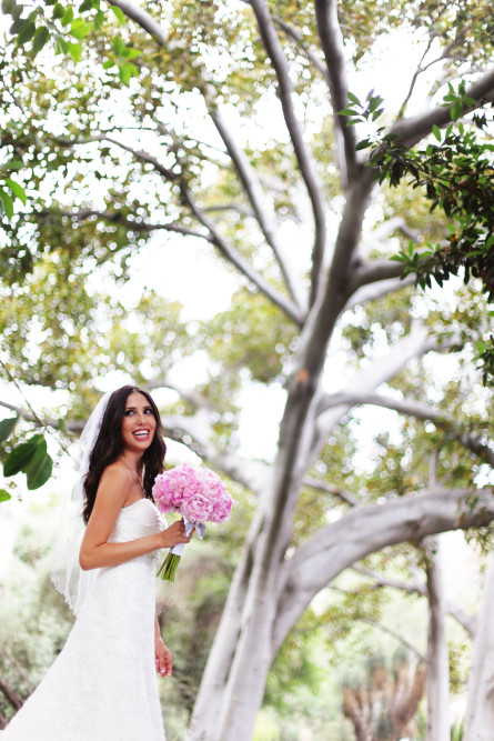 bride holding bouguet outdoors by tree